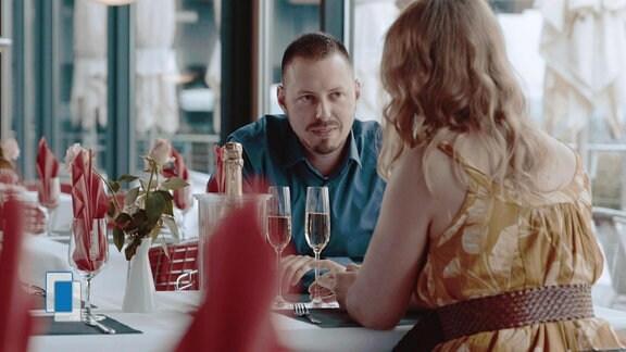 Ein Mann sitzt am Tisch und guckt eine Frau an.
