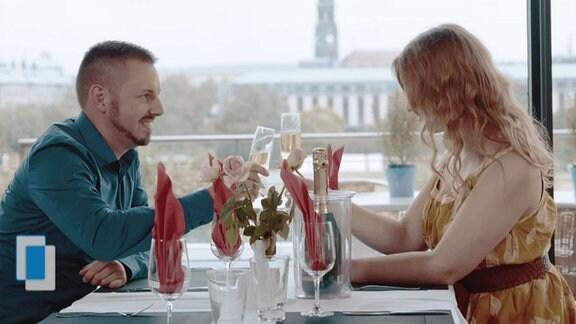 Paar sitzt sich im Restaurant gegenüber und prostet sich mit Sekt zu.