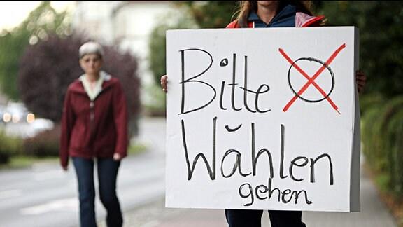 """Eine Frau hält ein Schild mit der Aufschrift """"Bitte wählen gehen"""""""