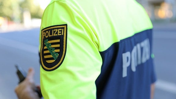 Das Emblem der sächsischen Polizei auf dem Ärmel eines T-Shirts.