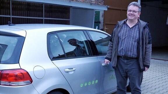 Der MDR SACHSEN Programmmacher Olaf Mierwaldt steht lächelnd neben einem Auto