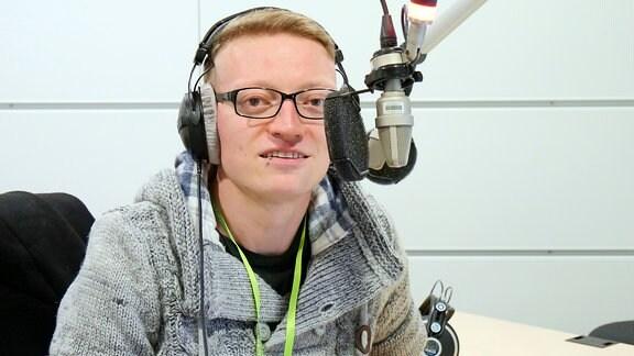Ein Mann mit Kopfhörern spricht in ein Mikrofon