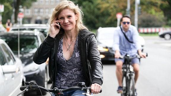 Radfahrerin telefoniert mit dem Handy im Straßenverkehr