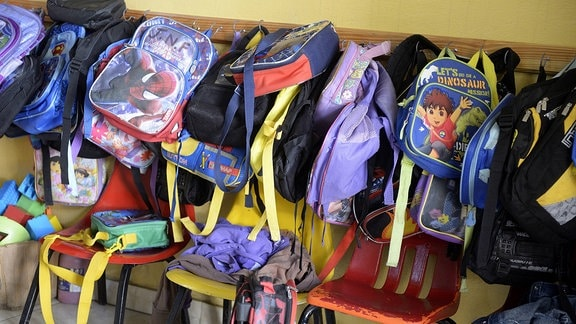 Kindergarten-Taschen hängen an der Wand.