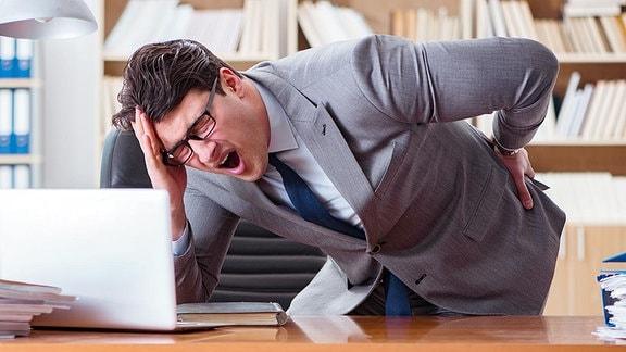 Ein Mann stützt sich auf einen Schreibtisch ab.