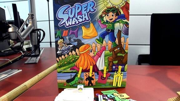 """Auf einem roten Tisch steht eine Schachtel mit der Aufschrift """"Super Wash"""", davor liegen Karten und bunte Teile"""