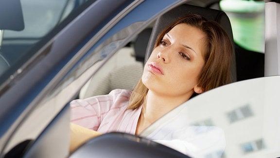 Frau sitzt gelangweilt in einem Auto.