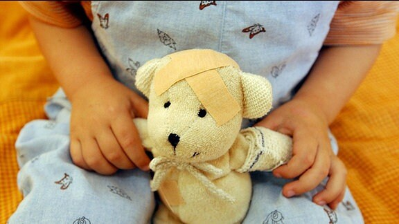 Ein Kind hält einen Teddy mit Pflaster auf dem Kopf und verbundenem Arm