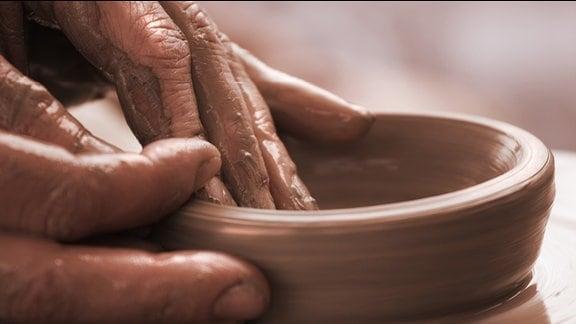 Hände formen Tongefäß auf Töpferscheibe