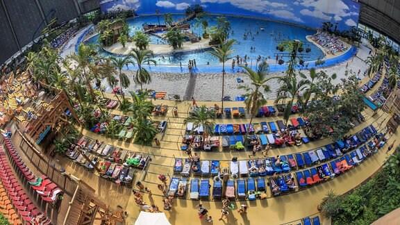 Palmen, Strand, Wasser und Besucher im Tropical Island.