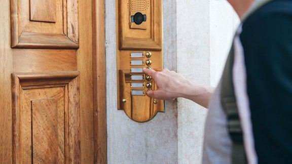 Ein Mensch klingelt vor einer Haustür an einer Gegensprechanlage