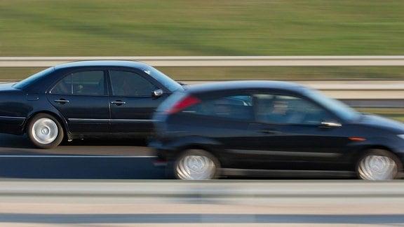 Auf einer Autobahn überholt ein Auto ein anderes