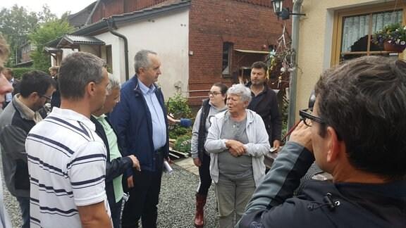 Sachsens Umweltminister Schmidt im Gespräch mit vom Hochwasser Betroffenen in der Emil-Claviez-Siedlung in Adorf.