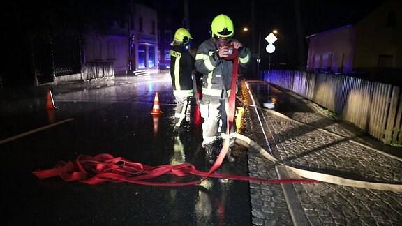 Ein Feuerwehrmann in Uniform hält einen roten Schlauch in der Hand. Auf dem Bild ist es nachts. Es ist dunkel. Es regnet. Die Straße ist Nass