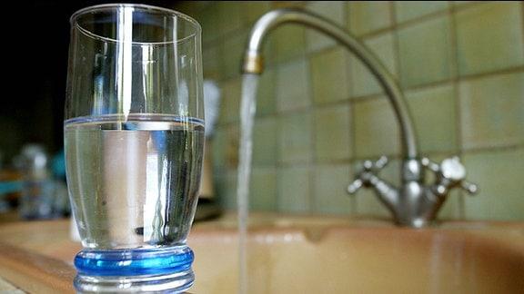 Ein Glas mit Wasser und im Hintergrund ein Wasserhahn