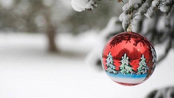 Eine rote Christbaumkugel an einer verschneiten Tanne