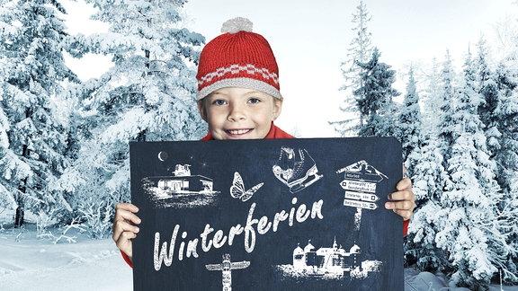Ein Junge mit roter Mütze hält ein Schild mit der Aufschrift Winterferien.