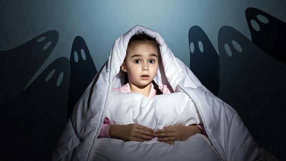 Ein Kind sitzt ängstlich unter einer Bettdecke