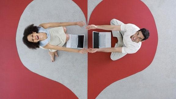 Eine Frau und ein Mann sitzen auf einem Teppich mit Herz-Muster vor ihren Laptops