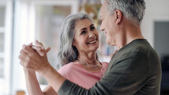 Glückliches, älteres, Paar tanzt in der Wohnung.