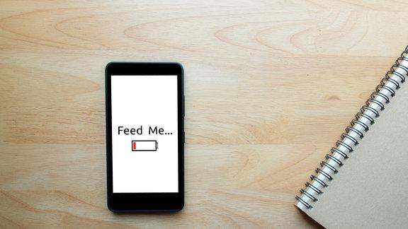 Auf Smartphone-Bildschirm wird leerer Akku angezeigt.