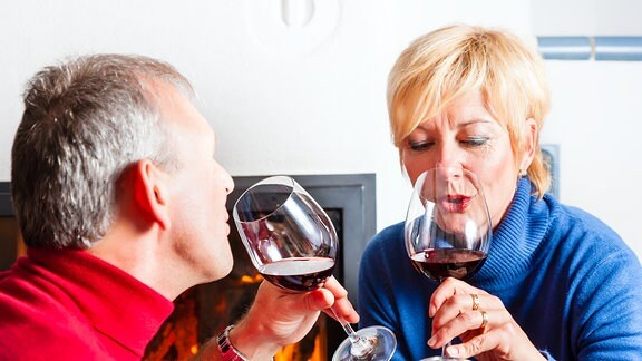 Zwei Menschen trinken Rotwein.