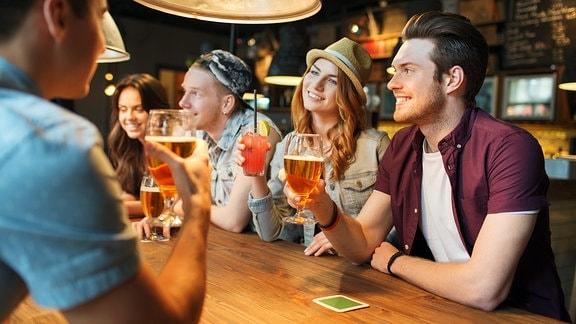 Junge Leute sitzen am Tresen und feiern mit alkoholischen Getränken.