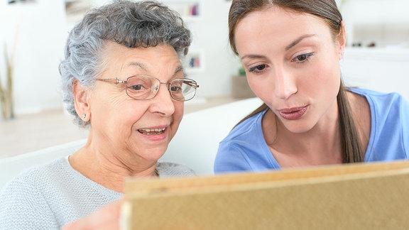 Eine ältere und eine junge Frau stehen nebenenander und schauen auf einen Plan.