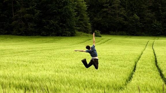 Mensch in einem Feld macht Luftsprünge