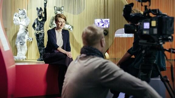 Eine Frau (Viktoria Krason) sitz vor einer Kamera