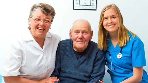 Ein alter Mann und zwei Pflegekräfte lachen in die Kamera