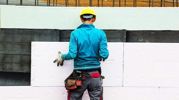 Bauarbeiter verkleidet ein Wand mit einer Platte.