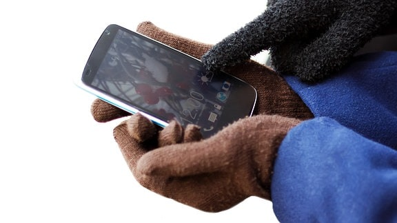 ein Finger im Handschuh zeigt auf den Bildschirm eines Smartphones