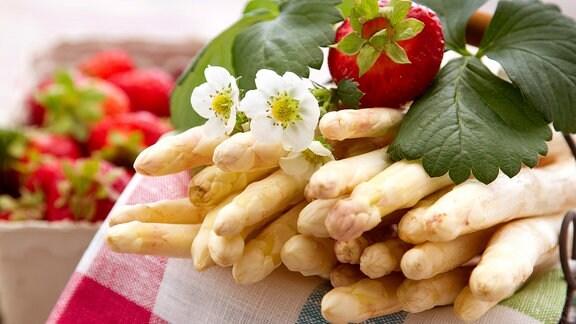 Frischer Spargel und Erdbeeren liegen zusammen auf einem Tisch.