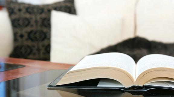 Ein Buch liegt aufgeschlagen auf einem Tisch