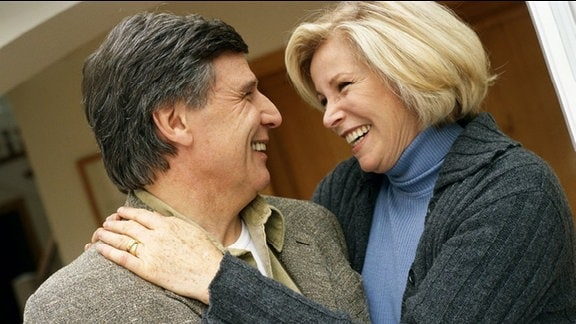 Ein Paar mittleren Alters liegt sich lächelnd in den Armen.