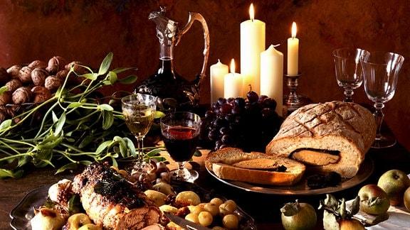 Ein weihnachtliches Festmal (Braten, Brot, Wein, ...) ist auf einem Tisch arrangiert.