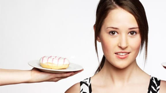 ein Mädchen zwischen einem angebotenen Donut und einem frischen Apfel