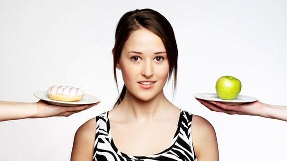 Symbolbild Diät: eine junge Frau, hin und her gerissen zwischen einem Donut und einem Apfel.