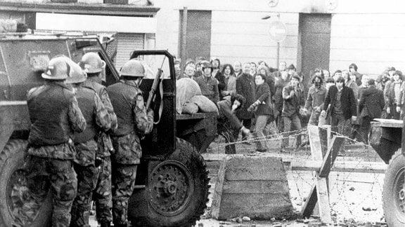 Soldaten stehen hinter einem Auto und im Hintergrund Passanten.