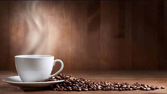 Ein Tasse Kaffe danaben liegen Kaffeebohnen.