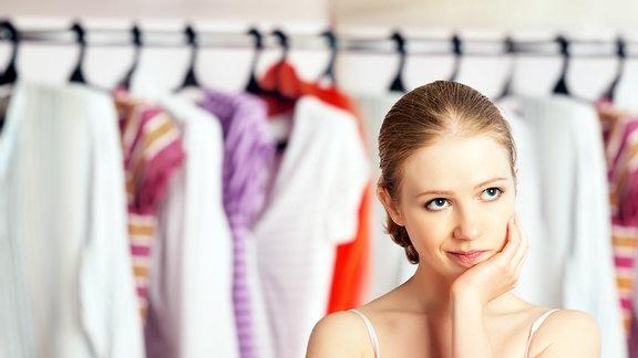 Eine Frau steht ratlos vor ihrem Kleiderschrank