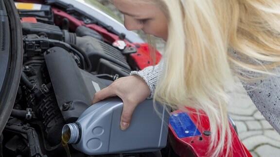 Eine junge Frau füllt frisches Öl in ihren PKW.