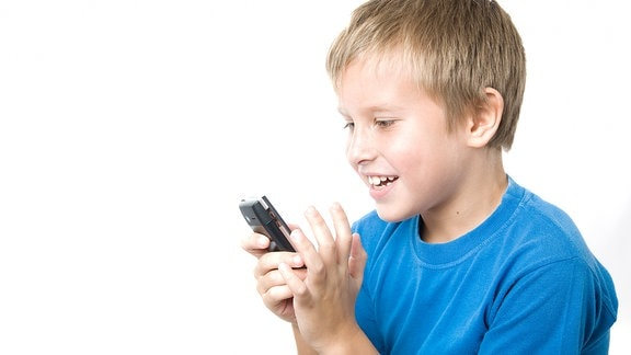 Ein Junge begutachtet ein Handy.