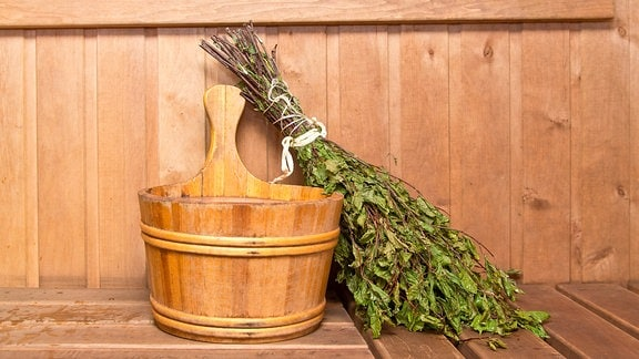 Ein Holzeimer in einer Sauna, daneben ein Bündel Birkenzweige