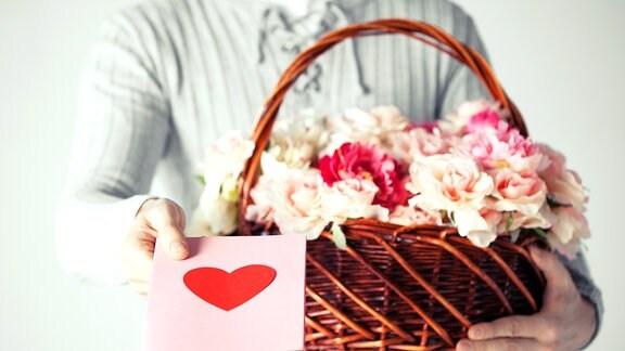 Ein Mann hält einen Korb mit Blumen und eine Karte mit einem Herz in der Hand.