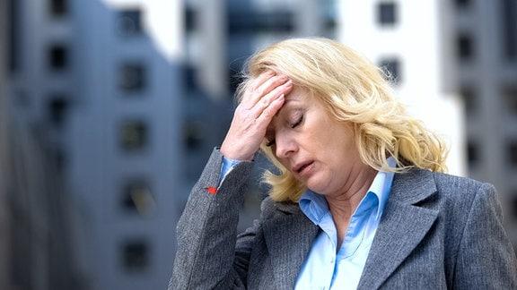 Erschöpft aussehende Frau greift sich an die Stirn