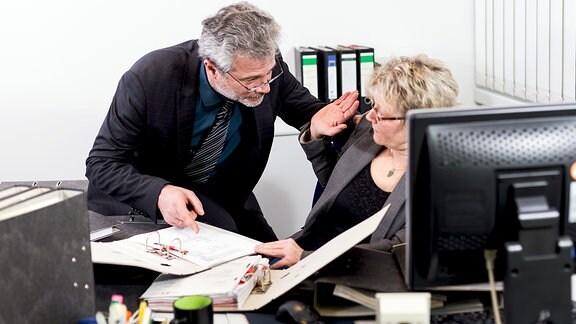 Symbolbild: Eine Angestellte wehrt die Annäherung ihres Chefs ab.