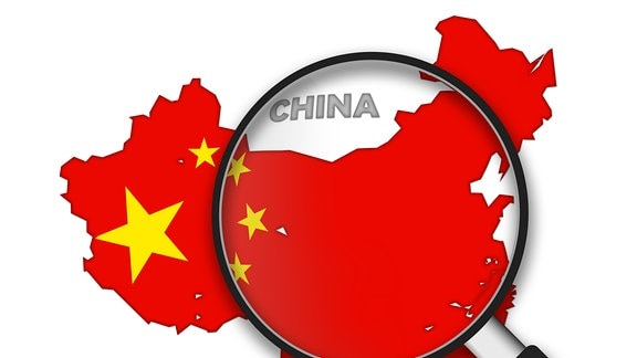 Der kartenmäßige Umriss Chinas unter einer Lupe. Die Fläche ist mit den Farben der chinesichen Flagge gefüllt.