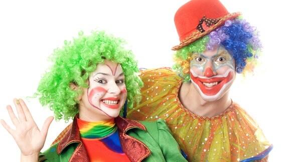 Eine Frau und ein Mann posieren in Clownskostümen